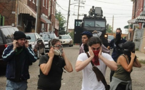 Michael Henninger / Post-Gazette 09/24/2009 Protesters continue to march while plugging their ears as police use a sonic weapon against an unlawful protest march that began at Arsenal Park in Lawrenceville and tried unsuccessfully to make its way to the Convention Center downtown on Thursday, Sept. 24, 2009.  Photo by Michael Henninger